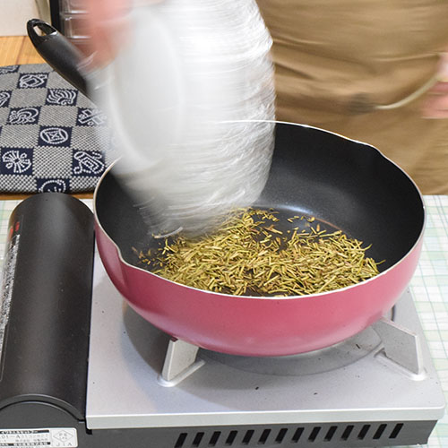 皿のお茶を手早くフライパンに平らに投入します 投入後1,2秒待ち少し煙が出始めたらフライパンを持ち上げ、火の上で素早く左右に振り続けます